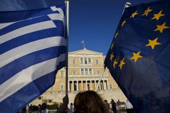 Mulheres com bandeiras da UE e da Grécia do lado de fora do Parlamento grego, em Atenas