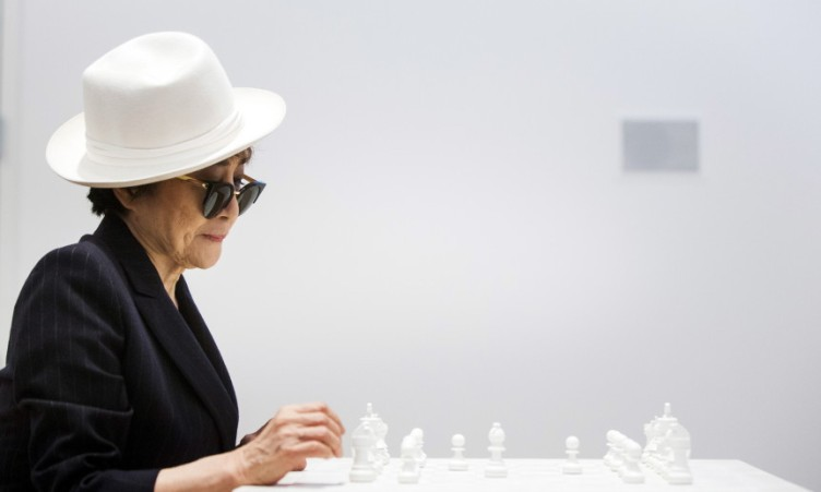 "Artist Yoko Ono interacts with the exhibit ""White Chess Set"" at the Museum of Modern Art exhibition dedicated exclusively to her work, titled ""Yoko Ono: One Woman Show, 1960-1971"", in New York May 12, 2015. REUTERS/Lucas Jackson"
